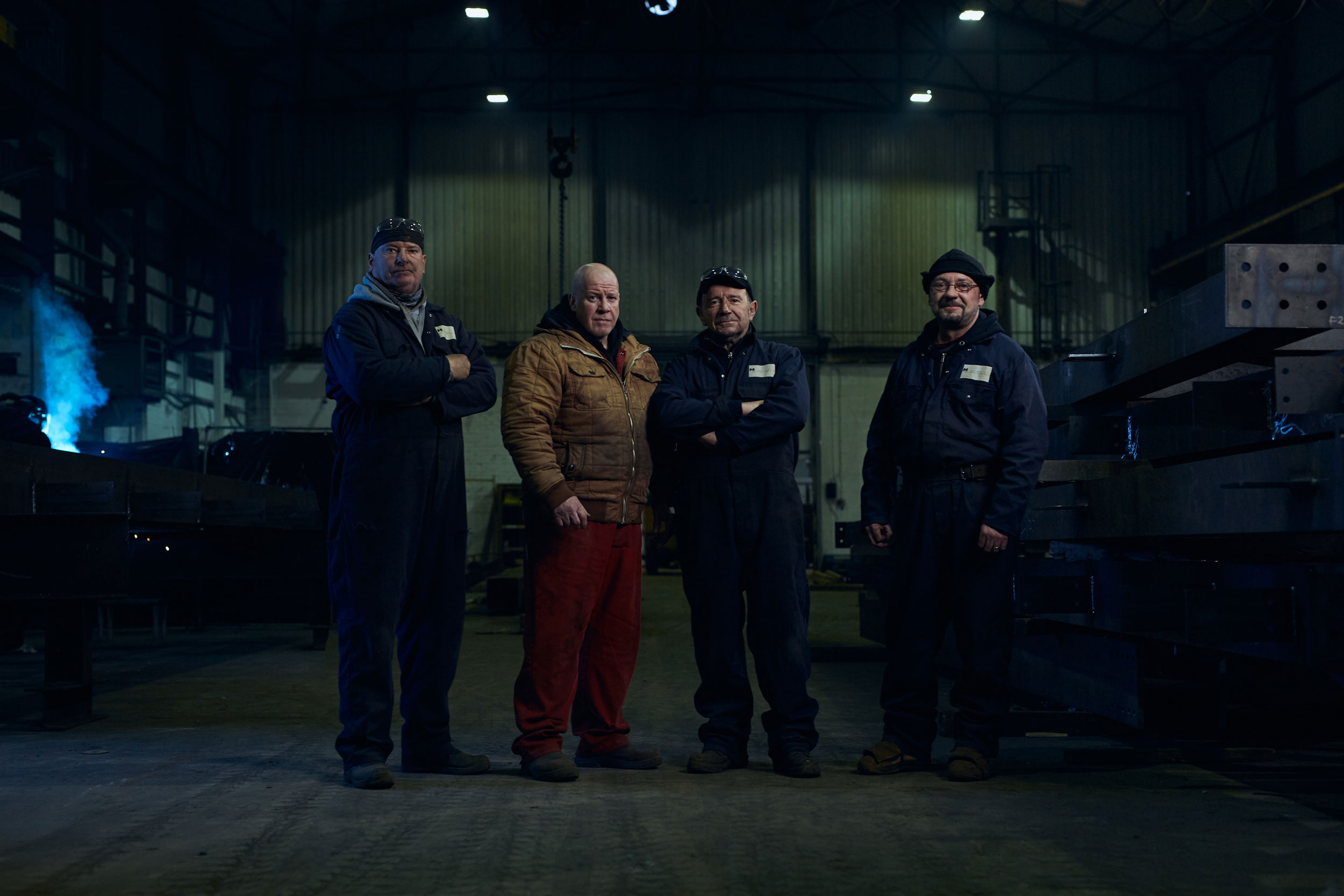 Four steelworkers stand in the dark factory they work in.