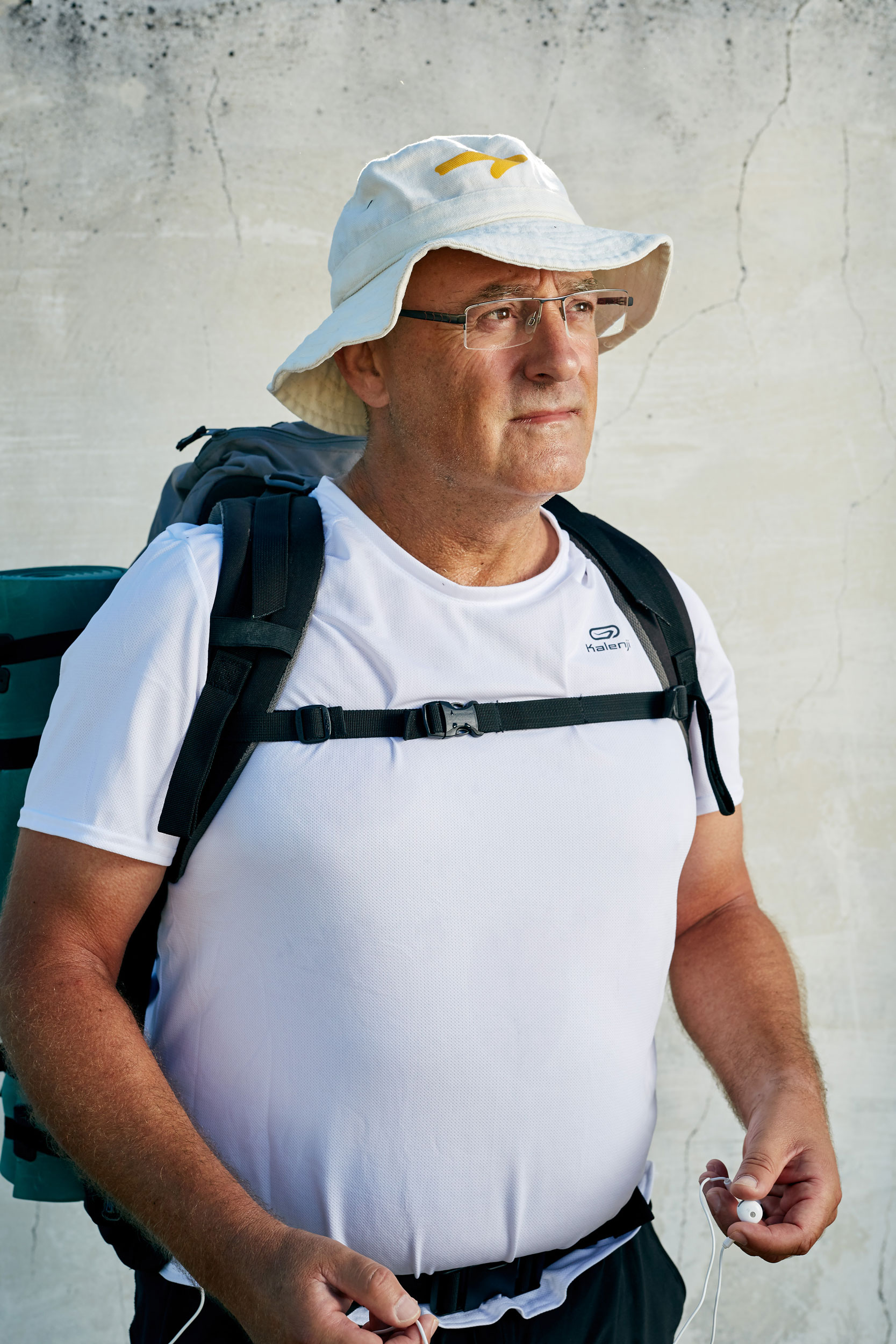Camino pilgrim male with white shirt and hat looks off contemplating his journey by documentary portrait photographer Duncan Elliott