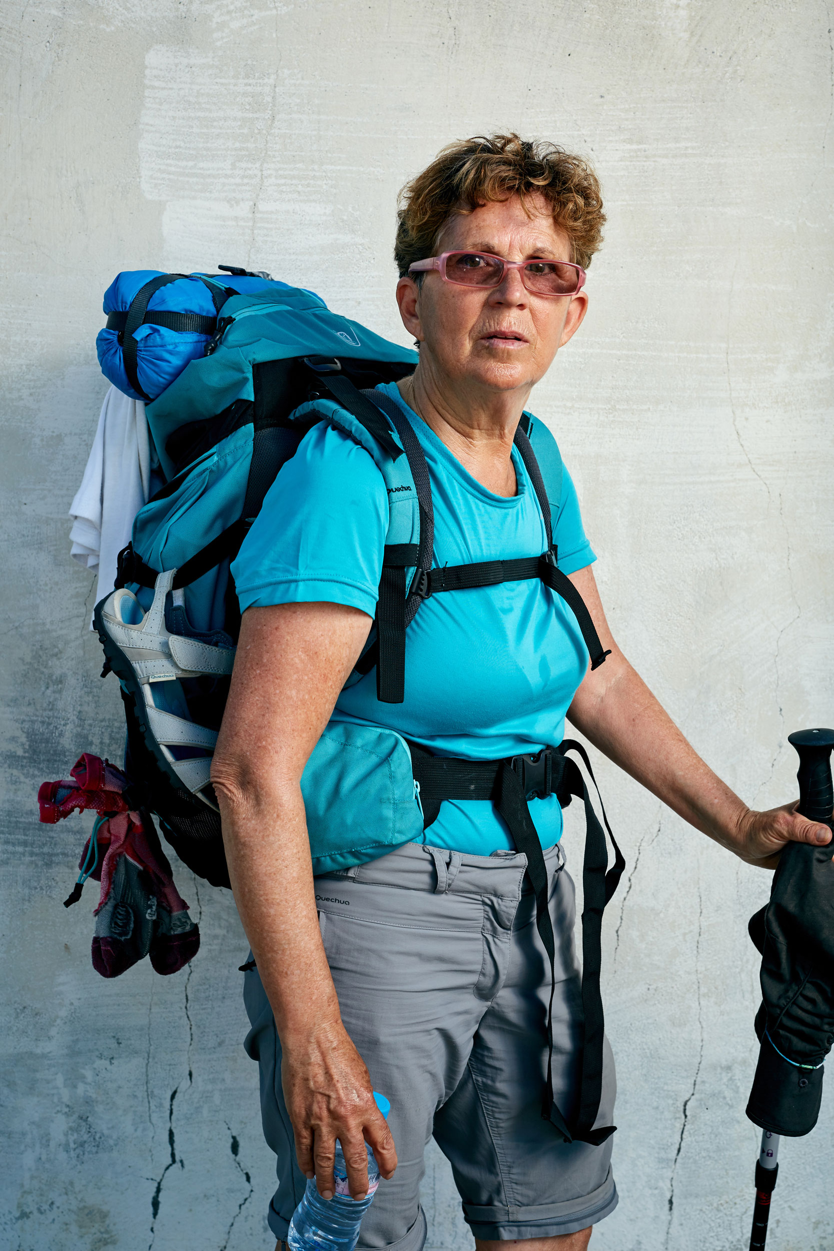 Camino pilgrim lady with a laden rucksack, water bottle and walking pole by documentary portrait photographer Duncan Elliott