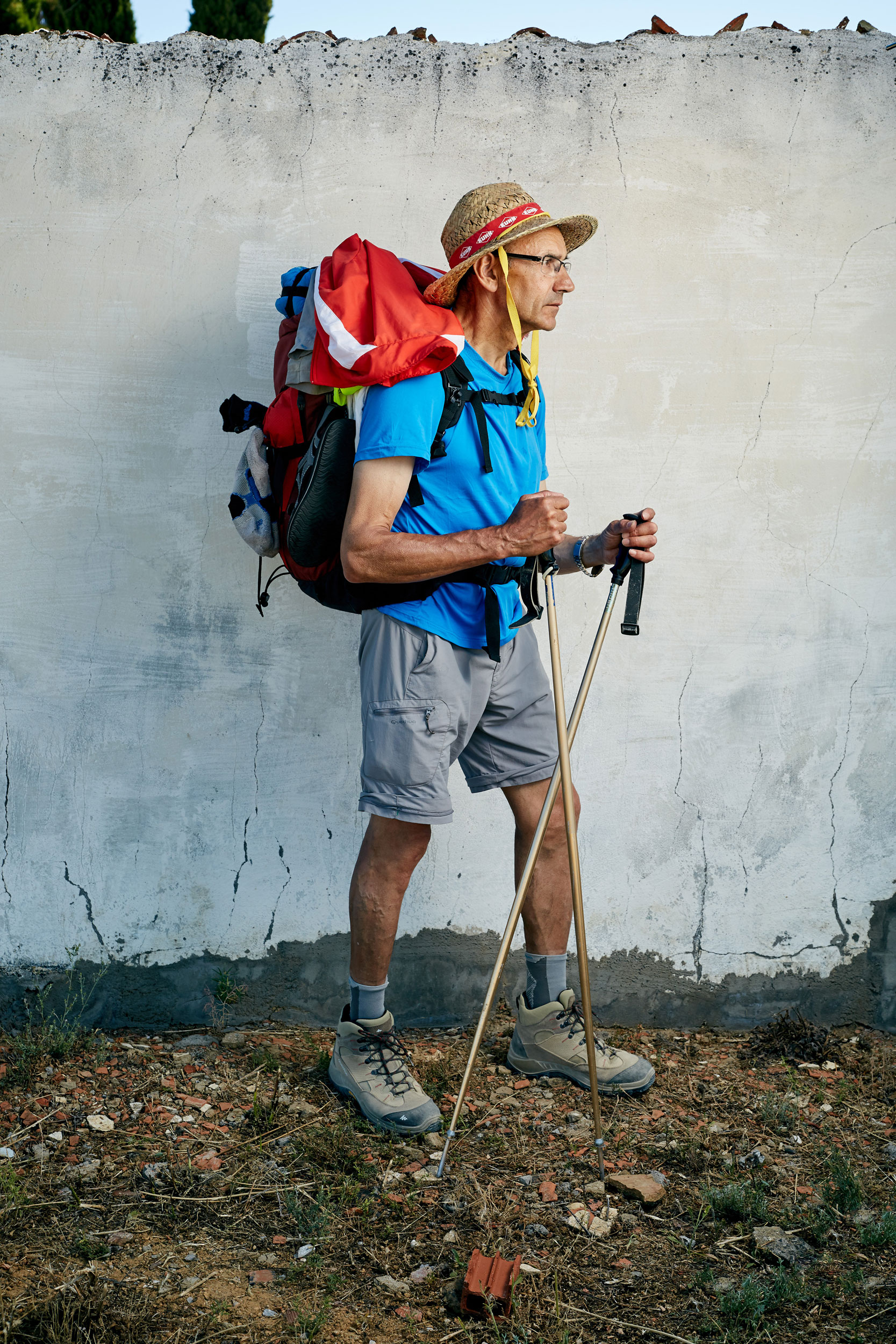 Camino pilgrim with blonde hair and straw hat stands beside a white wall with his walking stick and rucksack by documentary portrait photographer Duncan Elliott