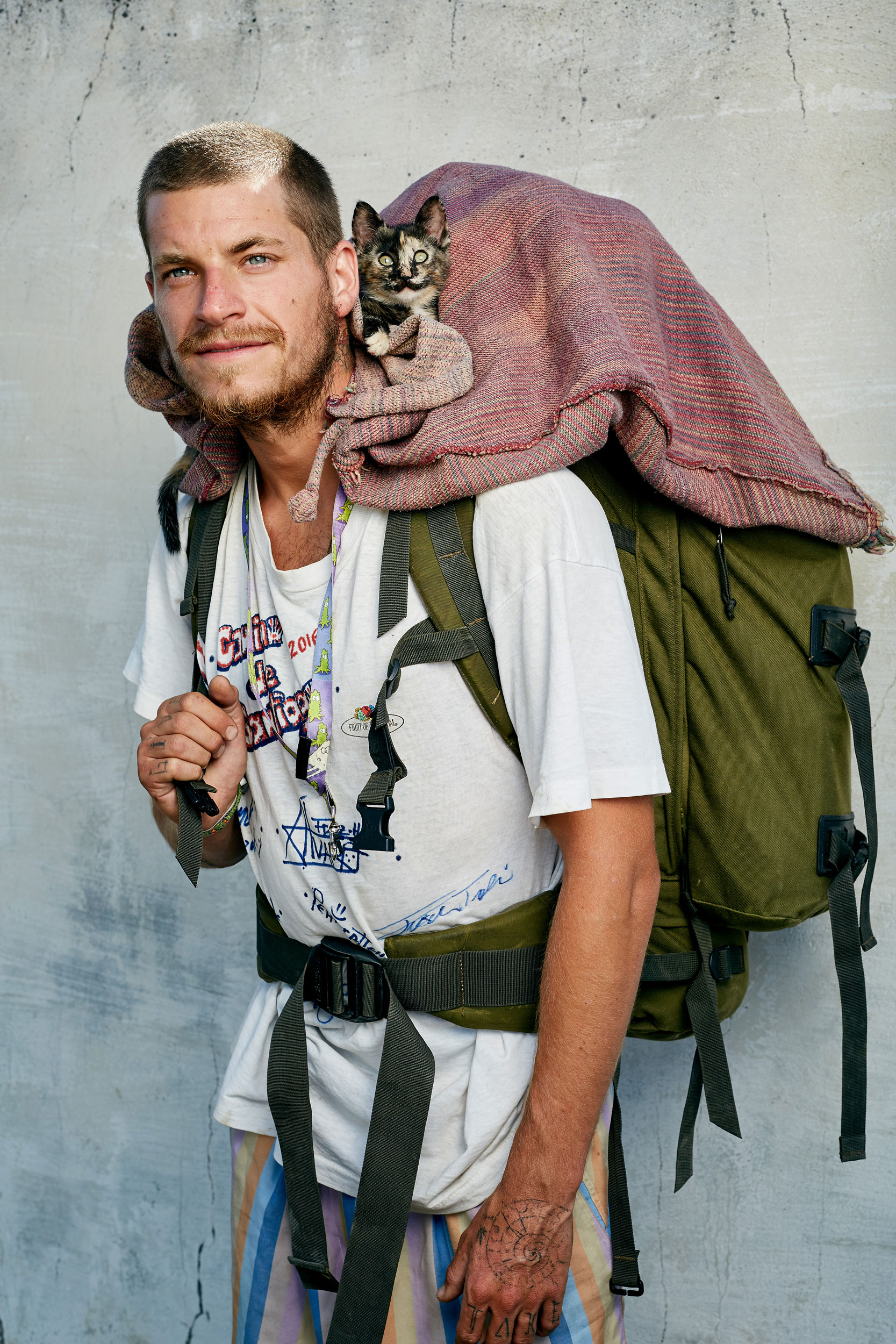 Camino pilgrim with a large rucksack and a kitten sat on his shoulders by documentary portrait photographer Duncan Elliott