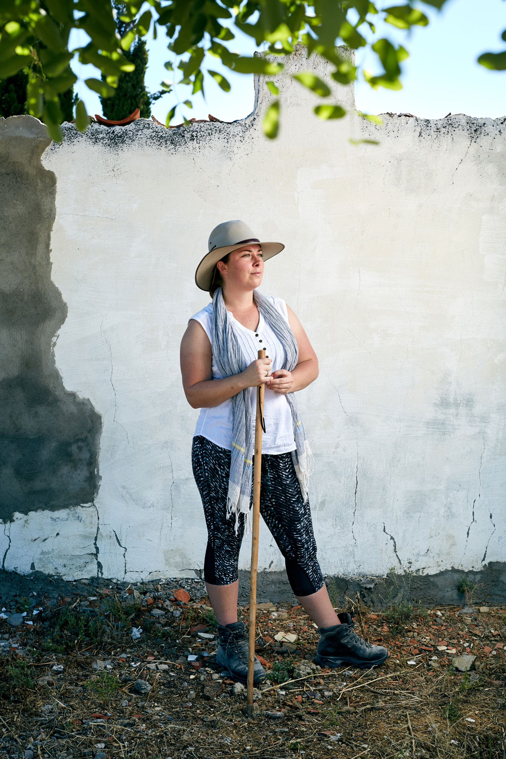 Camino pilgrim stands beside a white wall with her walking stick by documentary portrait photographer Duncan Elliott