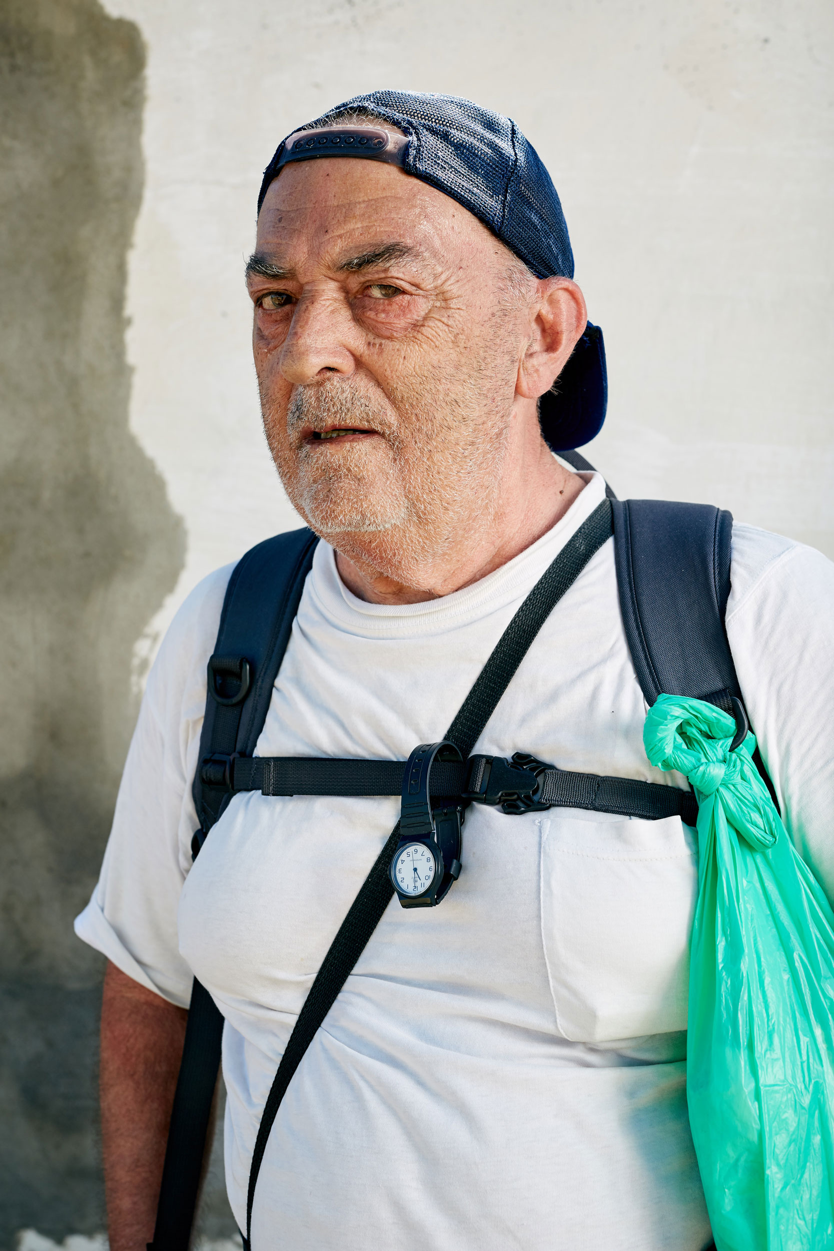 An elderly Camino pilgrim has a watch and plastic bag strapped to his rucksack by documentary portrait photographer Duncan Elliott
