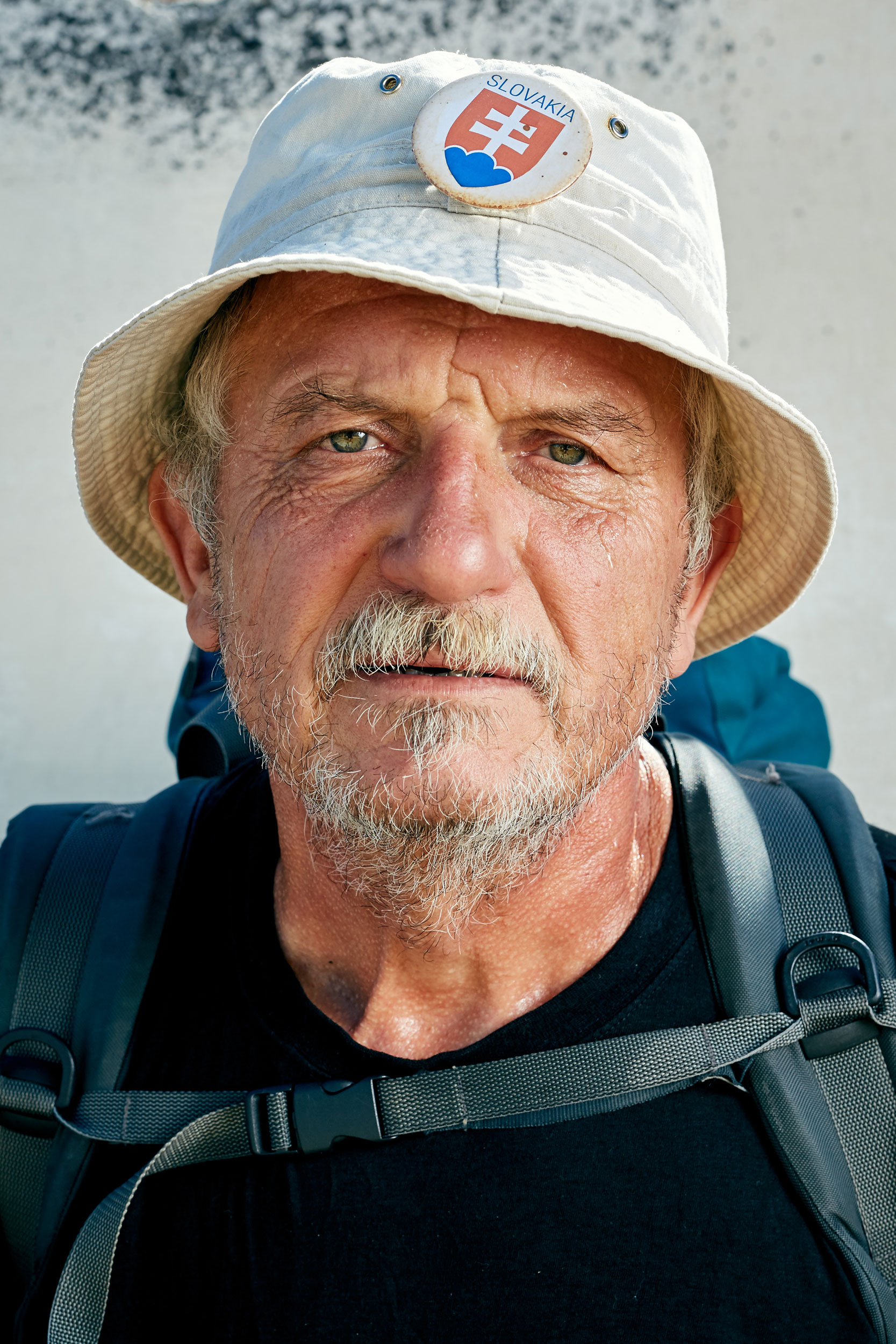 Camino pilgrim with a bucket hat and Slovakia badge by documentary portrait photographer Duncan Elliott