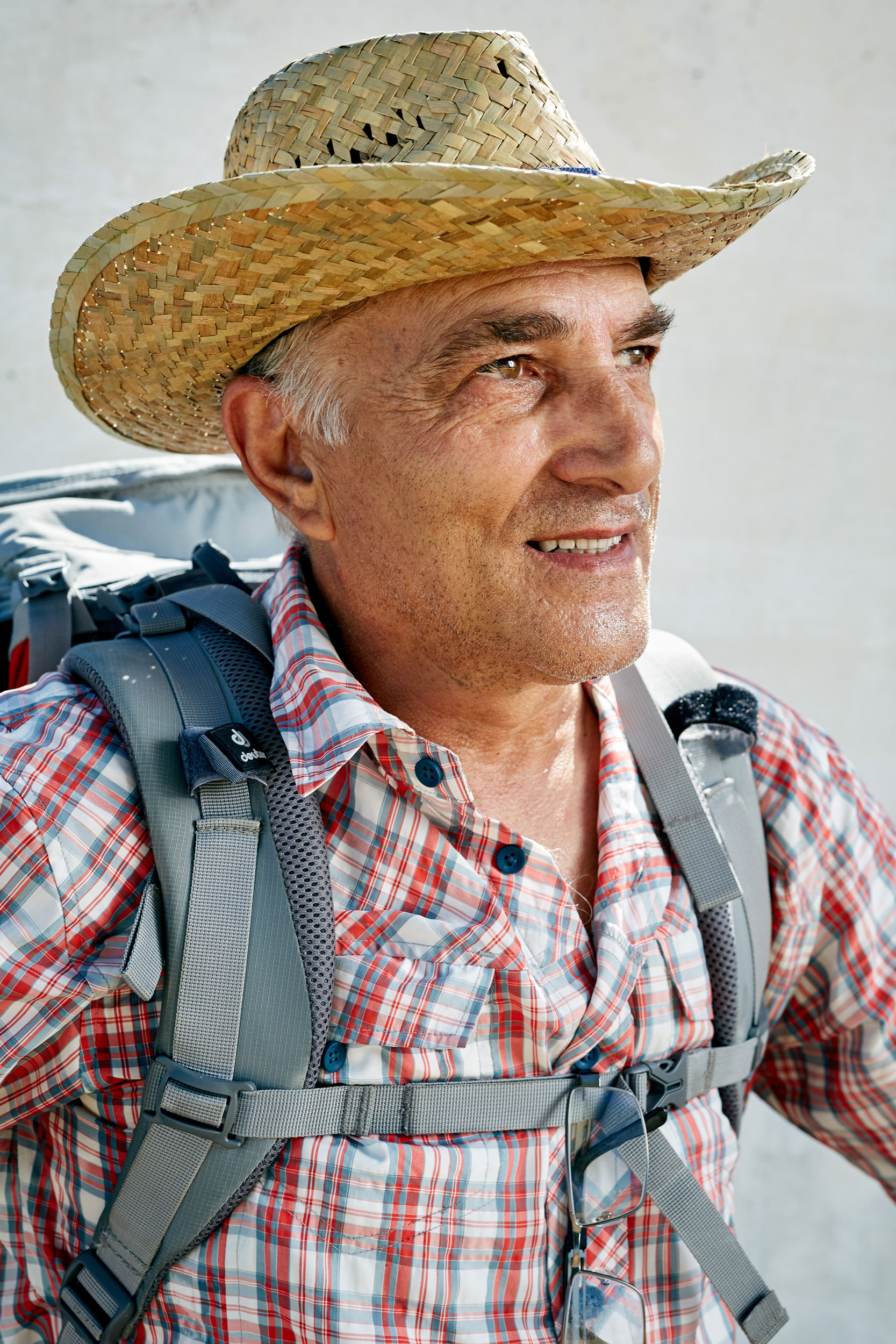 Camino pilgrim with a straw hat and flannel shirt by documentary portrait photographer Duncan Elliott