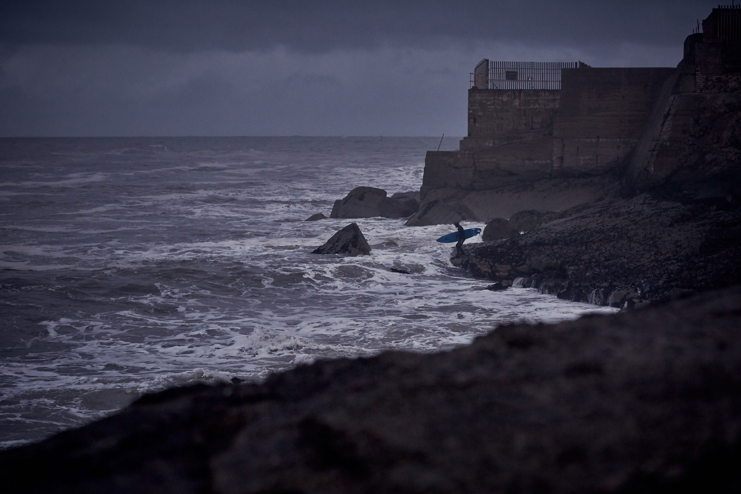 Surfer watches waves break against the rocks in front of him near Redcar