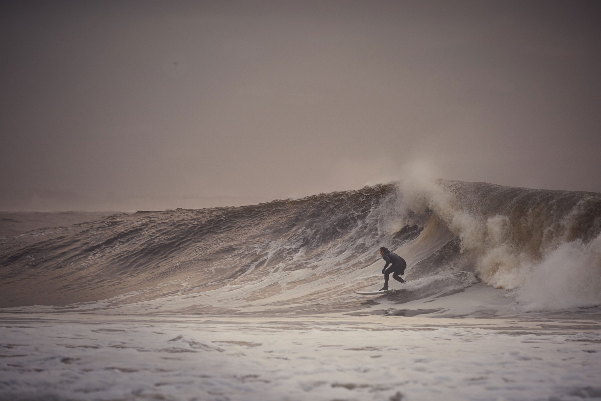 A surfer catches at wave during dusk.