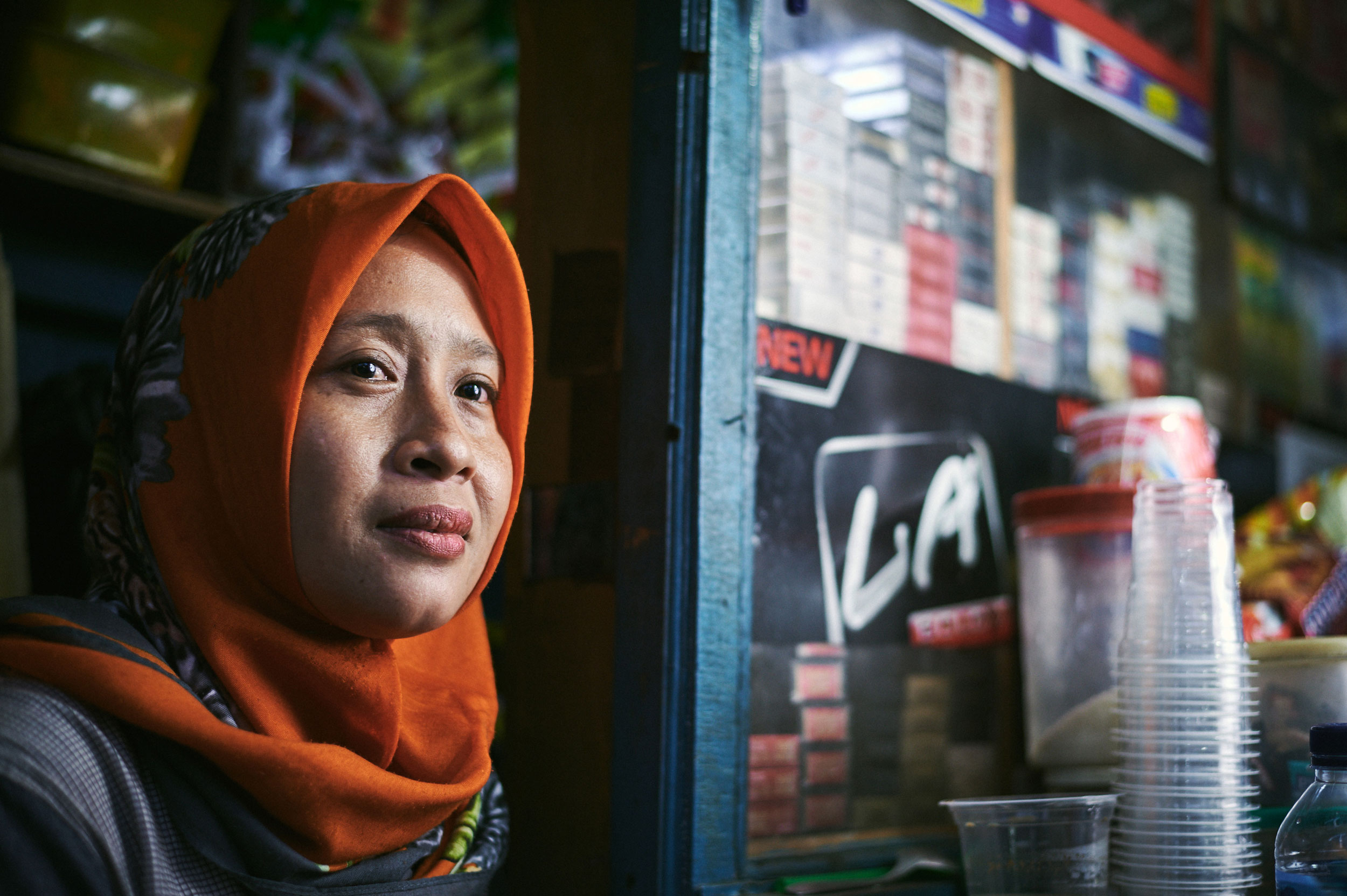 Woman in a red hijab at her street stall in Jakarta taken by Duncan Elliott